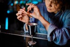 Femme ajoutant un scintillement de la brosse à un verre de cocktail avec la boisson alcoolisée photos stock
