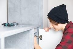 Femme ajustant la porte de meubles à la maison photos libres de droits