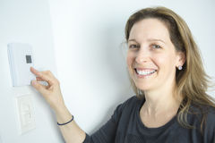 Femme ajustant le thermostat sur le système de chauffage domestique photo libre de droits