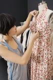 Femme ajustant le tissu sur le simulacre photos stock