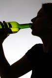 Femme alcoolique buvant d'une bouteille Image libre de droits