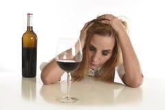 Femme alcoolique déprimée gaspillée blonde caucasienne buvant l'alcoolisme en verre de vin rouge photographie stock