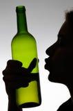 Femme alcoolique embrassant une bouteille de vin Images stock