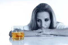 Femme alcoolique gaspillée et déprimée blonde caucasienne buvant malpropre en verre de whisky écossais bu photographie stock libre de droits