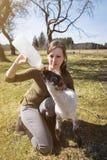 Femme alimentant un agneau avec du lait de bouteille, augmenter de main et un animal Images stock