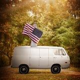 Femme américaine fière tenant le drapeau sur le vintage Van image libre de droits