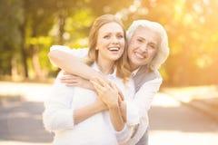 Femme amicale appréciant la promenade avec le retraité dans la place Image libre de droits