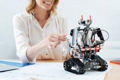 Femme animée communiquant avec le robot électronique dans le bureau Photos libres de droits