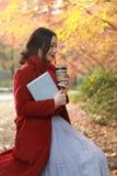 Femme anonyme appréciant la tasse de café à emporter le jour froid ensoleillé d'automne images stock