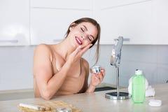 Femme appliquant des produits de beauté Images libres de droits
