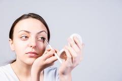 Femme appliquant l'eye-liner tout en regardant un miroir Photos stock