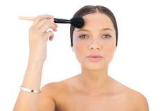 Femme appliquant la brosse de poudre sur le front Photo libre de droits