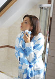 Femme appliquant la crème à sa peau Photos libres de droits