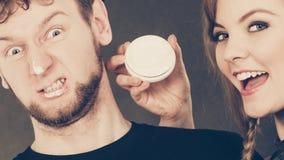 Femme appliquant la crème à son visage d'homme Photographie stock libre de droits