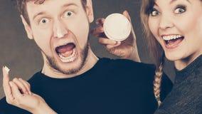 Femme appliquant la crème à son visage d'homme Photographie stock