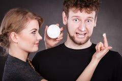 Femme appliquant la crème à son visage d'homme Photo libre de droits