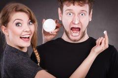 Femme appliquant la crème à son visage d'homme Photos libres de droits