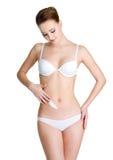 Femme appliquant la crème cosmétique sur l'abdomen Photographie stock