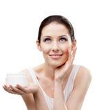 Femme appliquant la crème d'humidité à partir du conteneur sur le visage photos libres de droits