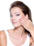 Femme appliquant la crème de crème hydratante sur le visage Photos libres de droits