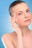 Femme appliquant la crème de levage sur le visage, au-dessus du bleu Images libres de droits