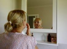 Femme appliquant la crème de visage Photo libre de droits