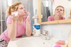 Femme appliquant la crème de visage avec son doigt image libre de droits