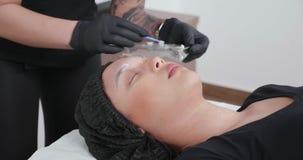 Femme appliquant la crème engourdissante sur les sourcils avant le retrait de tatouage banque de vidéos