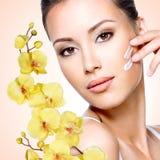 Femme appliquant la crème sur le visage Image libre de droits
