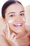 Femme appliquant la crème sur son visage Images libres de droits