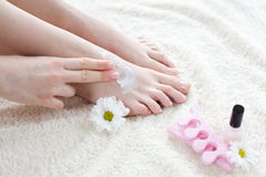 Femme appliquant la crème sur ses pieds Photos libres de droits