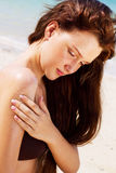 Femme appliquant la lotion de bronzage Photographie stock libre de droits