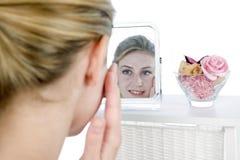 Femme appliquant la masque de beauté dans le miroir Photographie stock libre de droits