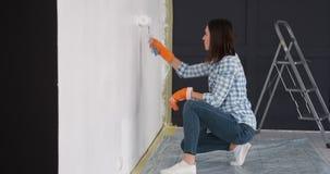 Femme appliquant la peinture utilisant le rouleau sur le nouveau mur d'appartement banque de vidéos