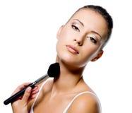 Femme appliquant la poudre sur le cou avec le balai Image stock