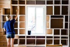 Femme appliquant la première couche de peinture sur une bibliothèque en bois Photos libres de droits