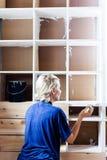 Femme appliquant la première couche de peinture sur une bibliothèque en bois Photographie stock