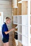Femme appliquant la première couche de peinture sur une bibliothèque en bois Photo stock
