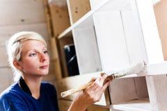 Femme appliquant la première couche de peinture sur une bibliothèque en bois Image stock