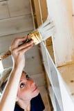 Femme appliquant la première couche de peinture sur une bibliothèque en bois Photo libre de droits