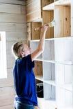 Femme appliquant la première couche de peinture sur une bibliothèque en bois Images stock