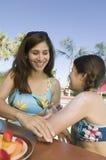 Femme appliquant la protection solaire à la fille (7-9) à la piscine. images stock