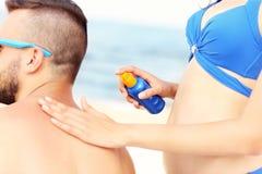 Femme appliquant la protection solaire au dos de son homme Image libre de droits