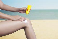 Femme appliquant la protection solaire sur sa jambe avec le fond de mer photo stock