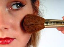 Femme appliquant le blusher Photographie stock