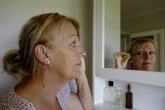 Femme appliquant le maquillage Photographie stock libre de droits