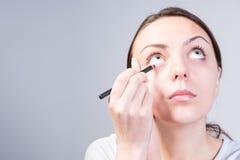 Femme appliquant le maquillage d'eye-liner tout en recherchant Images libres de droits