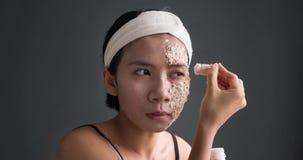 Femme appliquant le maquillage effrayant de zombi sur le visage banque de vidéos