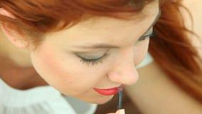 Femme appliquant le maquillage sur la plage banque de vidéos