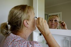 Femme appliquant le mascara Photo stock